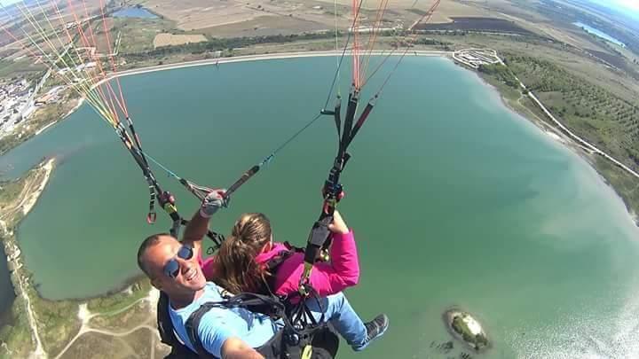 Тандемен полет с парапланер над езеро в България.
